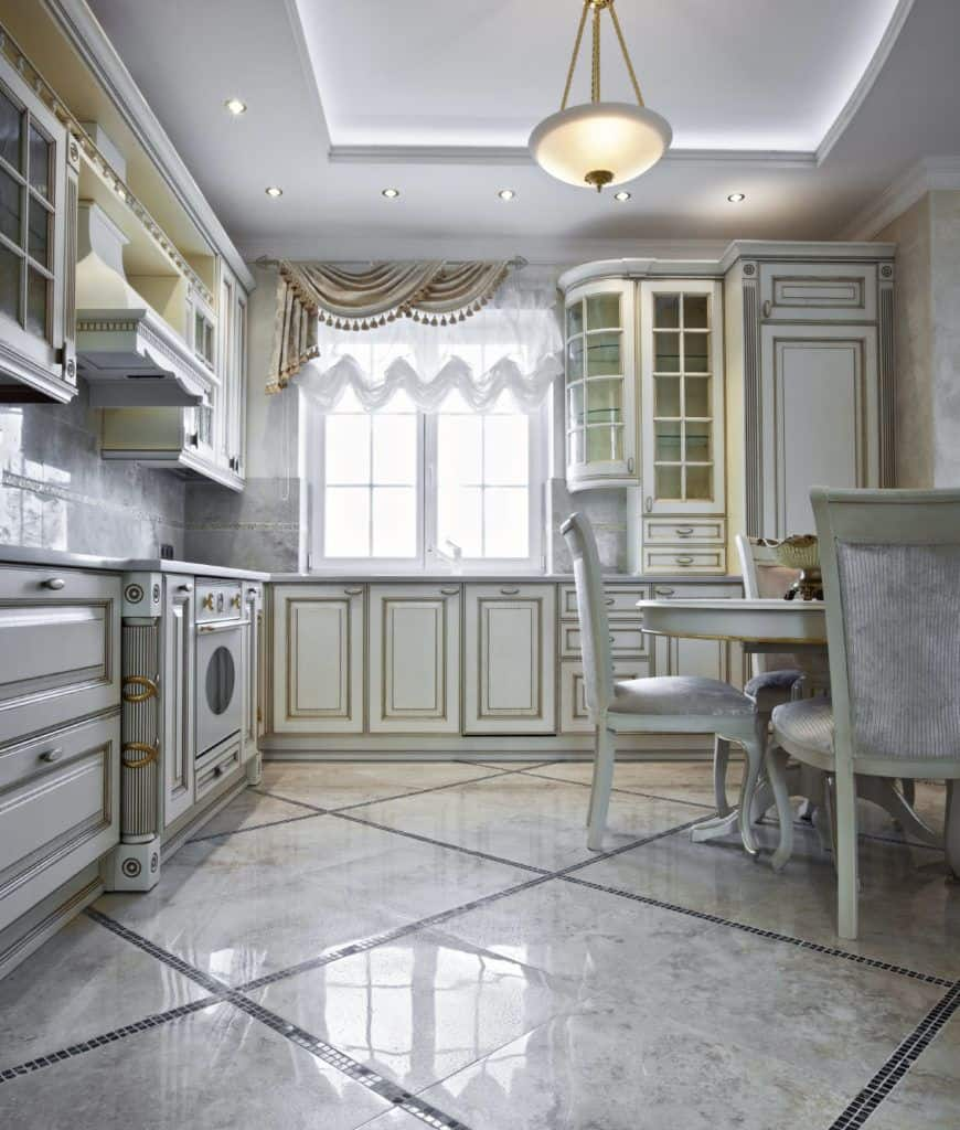 Elegant kitchen with a white oven and ornate cabinetry illuminated by a pendant light that hung from the tray ceiling. There's a round dining table on the side surrounded with upholstered chairs.