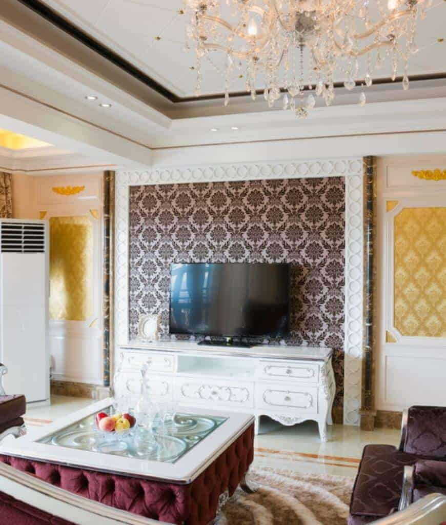 Fabulous living room clad in brown and gold classy wallpapers showcases a television that sits on a white ornate stand and a burgundy tufted center table lighted by a glam chandelier.