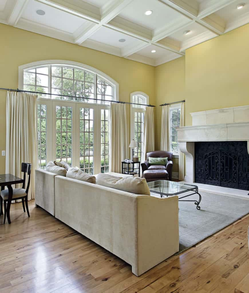 Yellow living room offers a gray sofa and marble fireplace wrapped in an ornate wrought iron screen. It is illuminated by recessed lights fitted on the coffered ceiling.