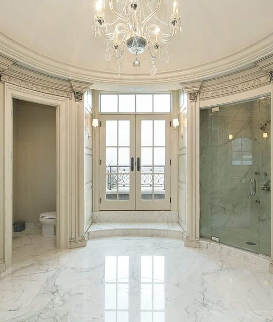 Elegant primary bathroom offers a walk-in shower and toilet area with a french door in the middle that opens to the balcony framed with ornate railing.