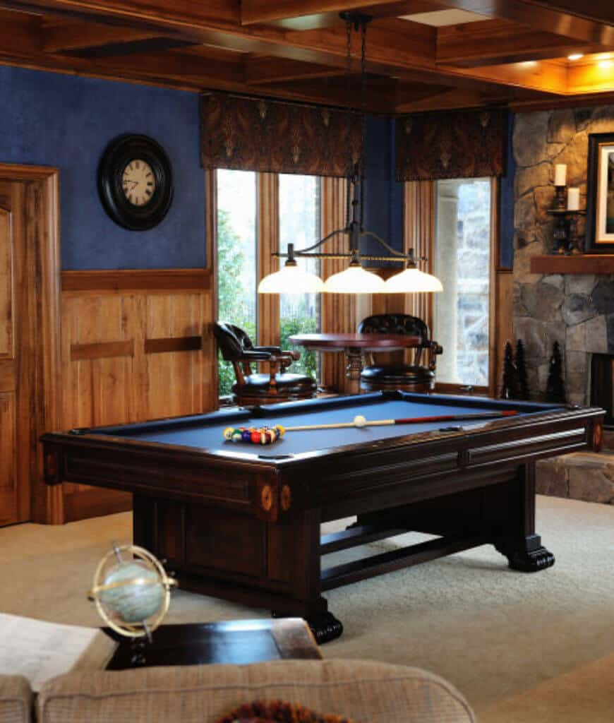 Craftsman man cave with a pool table in the middle illuminated by a pendant light that hung from the coffered ceiling. There's a seating area by the full height windows covered in patterned valences.