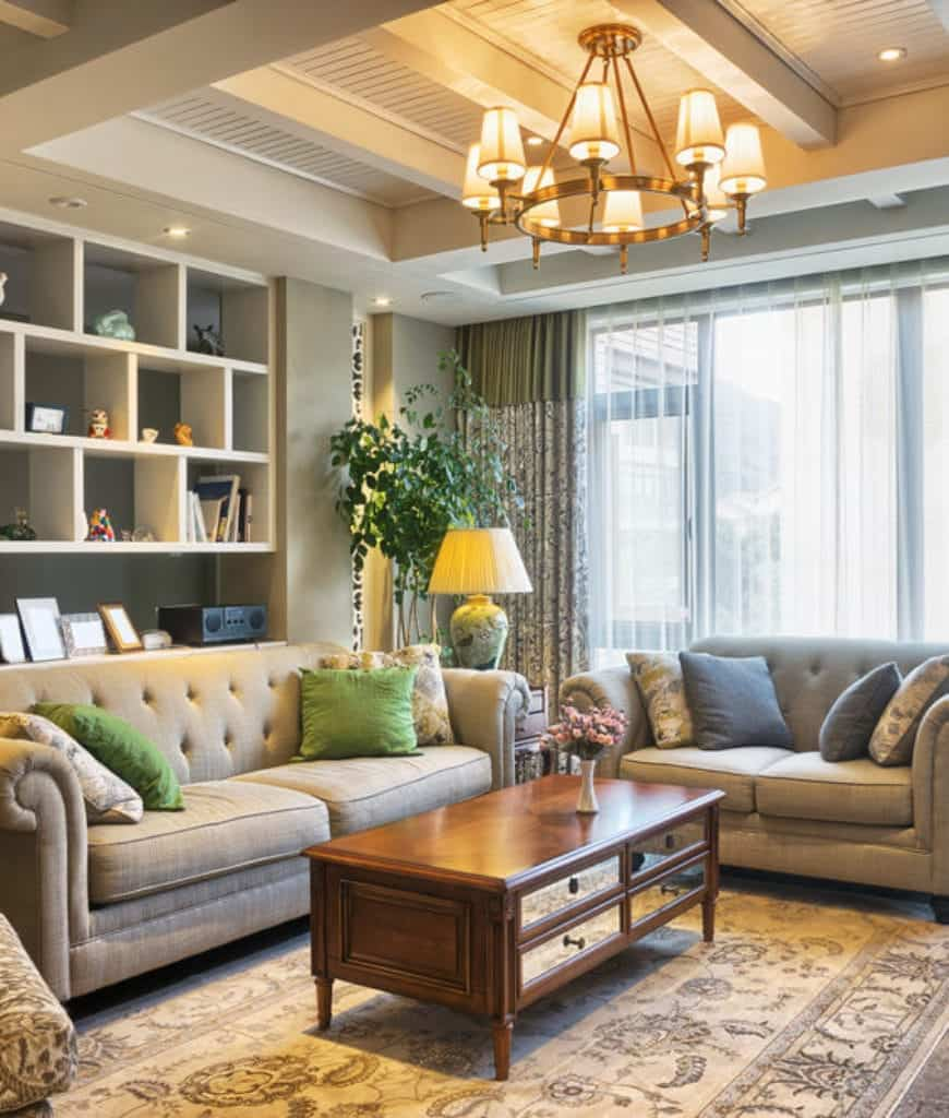 Well-lit living room showcases gray chesterfield sofas and a wooden coffee table illuminated by a wrought iron chandelier that hung from the shiplap coffered ceiling.