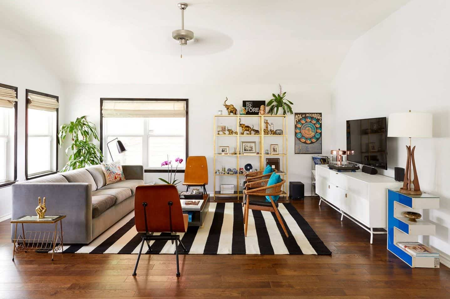 Tropical living room with a gray sectional and wooden chairs surrounding the dark wood coffee table that sits on a striking striped rug. It includes open shelving and television on a white wooden stand.