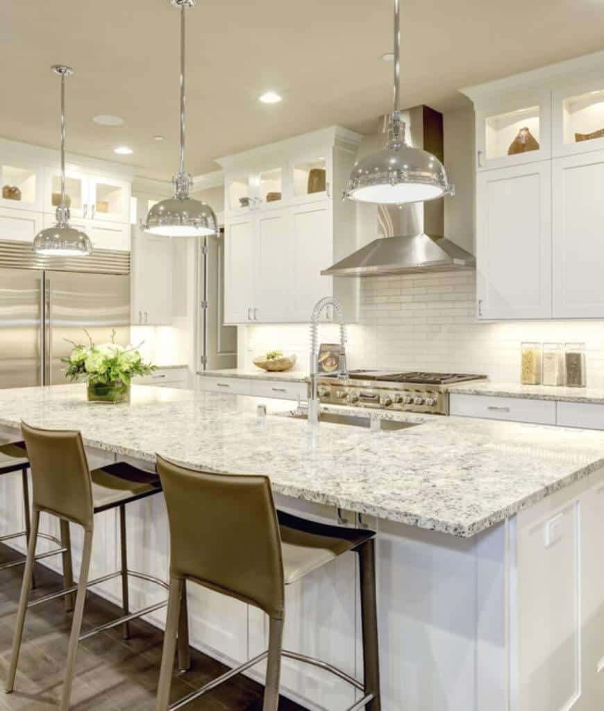 Well-lit kitchen with chrome pendant lights and a stainless steel range hood fixed on the white subway tile backsplash. It includes an island bar lined with counter chairs and fitted with a sink and pull down sprayer.