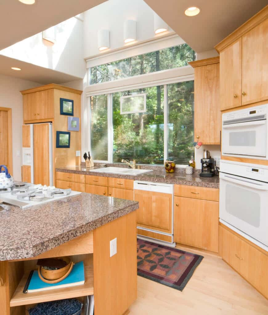 Bright kitchen with light hardwood flooring and glass paneled windows overlooking a serene outdoor view. It includes white appliances, wooden cabinetry and a marble top kitchen island with built-in shelving.