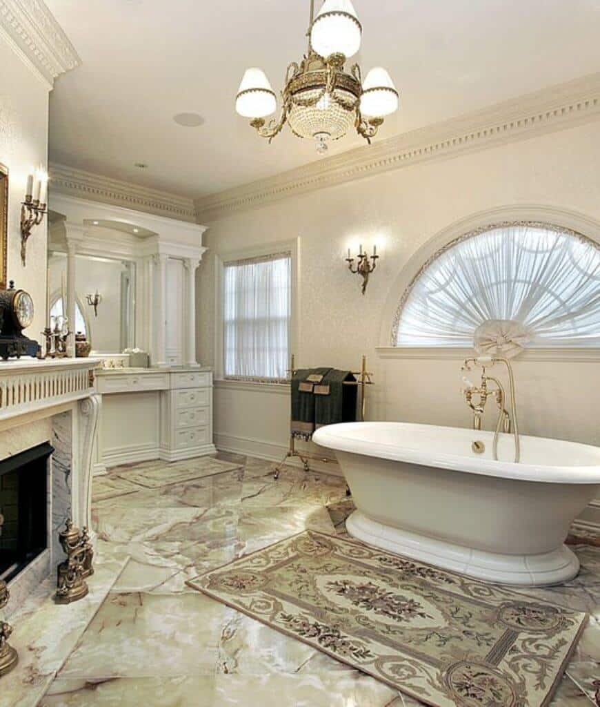 Deluxe master bathroom showcases a fireplace with marble surround tiles and a white vanity facing the freestanding tub with brass faucet and towel rack.
