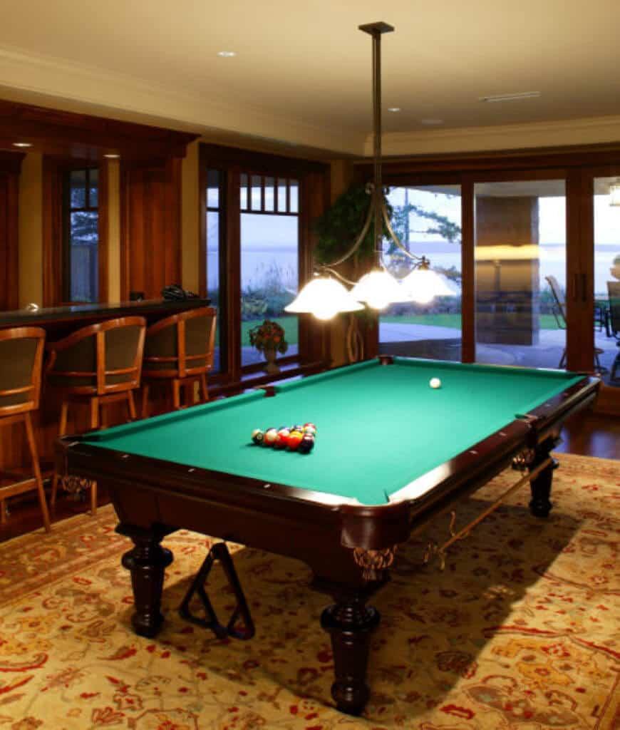 A wrought iron pendant hangs over the pool table on a floral rug in this room with a bar area enclosed in full height glazing.