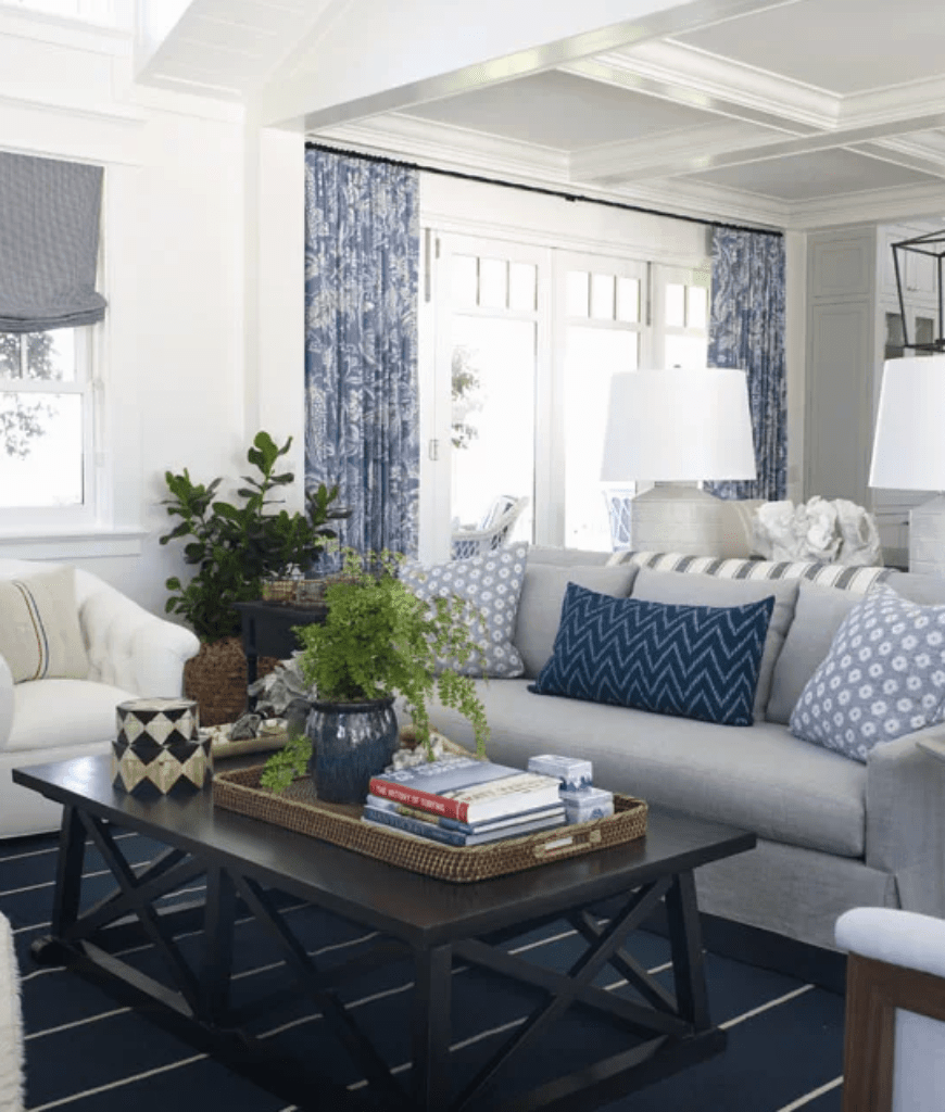 A fresh living room featuring a gray sofa accented with floral and chevron pillows along with a black coffee table that sits on a deep blue striped rug.