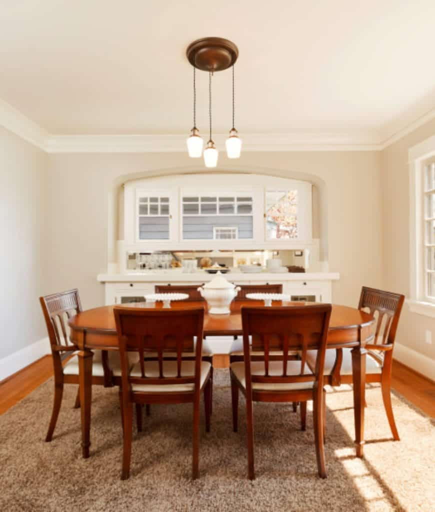 Glass pendants illuminate this dining room featuring an oval-shaped dining table and wooden chairs fitted with white cushions and sit on a beige shaggy rug.
