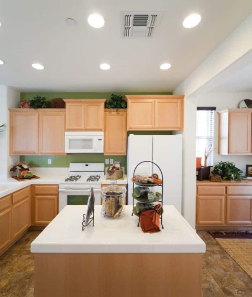 A charming kitchen with smooth wooden cabinetry and white appliances fixed to the moss green accent wall. It includes a central kitchen island topped with a glass jar and metal racks.