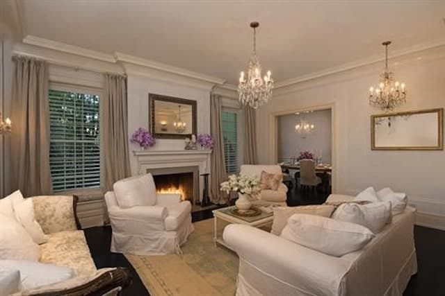 Classy living room showcases a monochromatic color scheme for a unified look. It has white skirted sofa and matching armchairs lighted by fancy chandeliers.