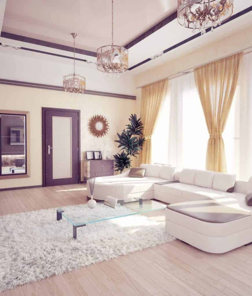 Gorgeous living room decorated with a sunburst mirror and fabulous chandeliers that hung over the white sleek sofa and glass coffee table on a shaggy rug.