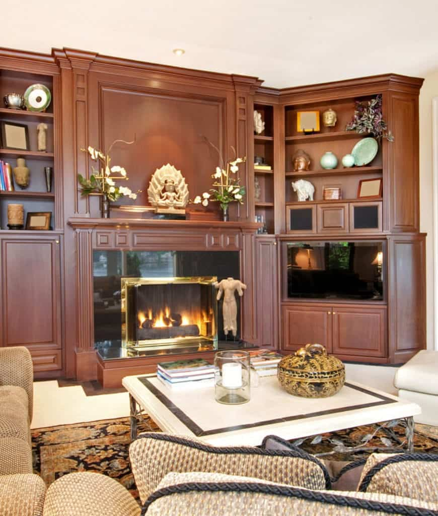 Sophisticated living room showcases built-in shelving filled with various decors and fitted with an elegant fireplace.