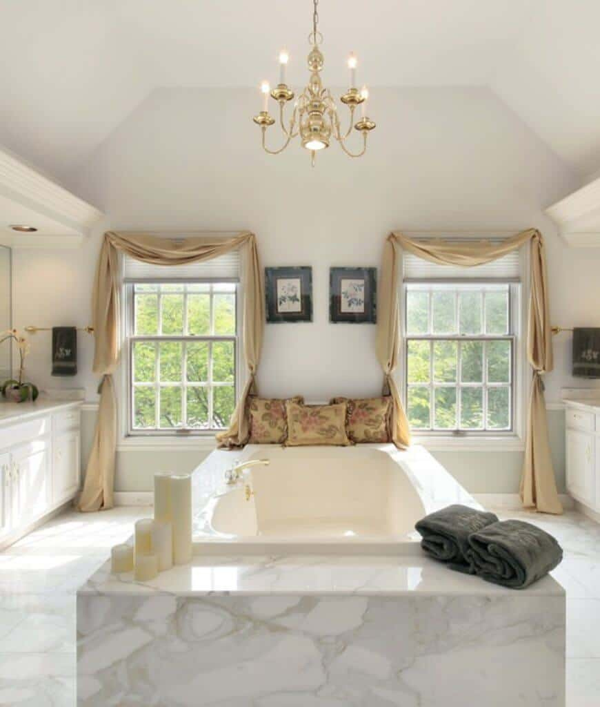 Charming primary bathroom decorated with a pair of wall arts and lovely pillows that lay on the marble bathtub in between framed windows and white vanities. A brass candle chandelier is the focal point of this symmetrical bathroom.