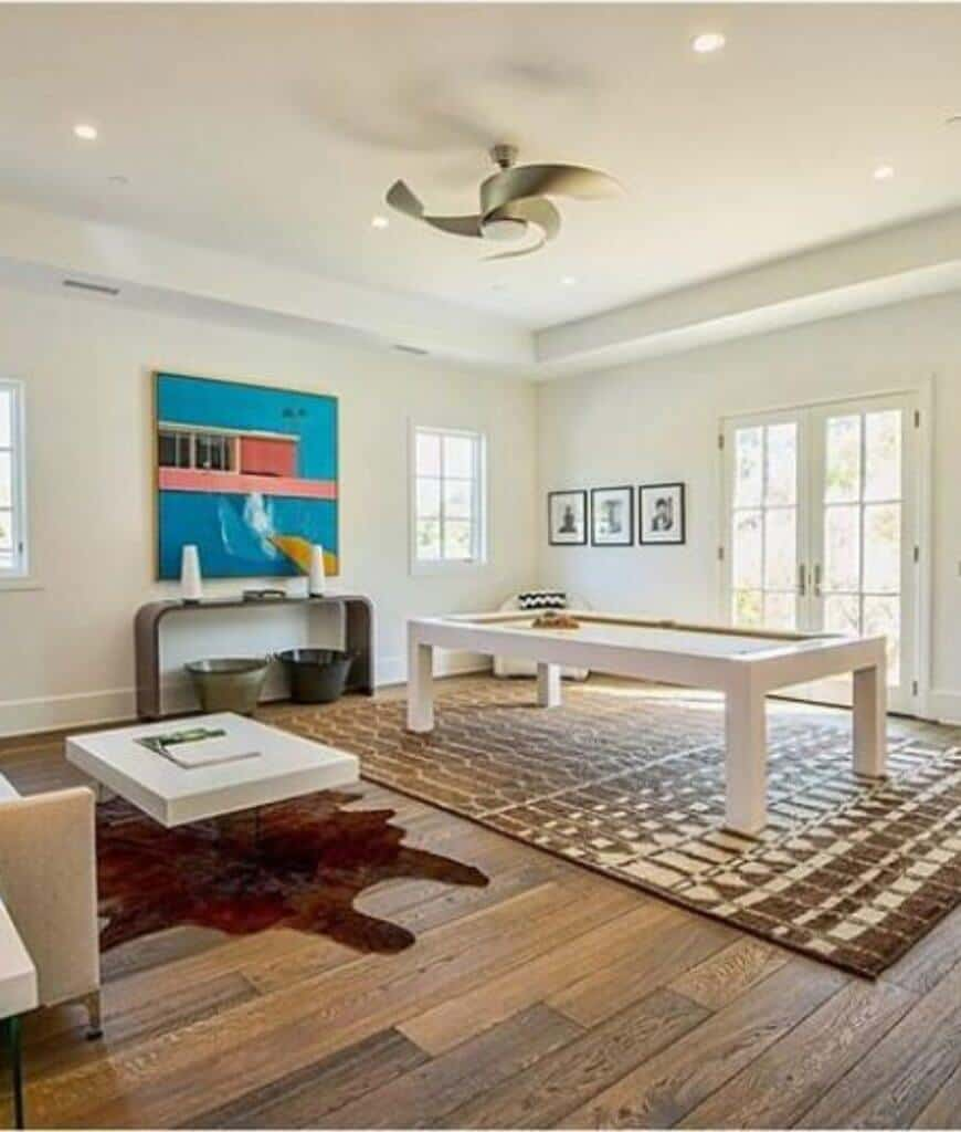 Family room decorated with black framed wall arts and a blue canvas mounted above the console table. There's a white chair in the corner complementing with the coffee table on a cowhide rug along with white pool table across the French door.
