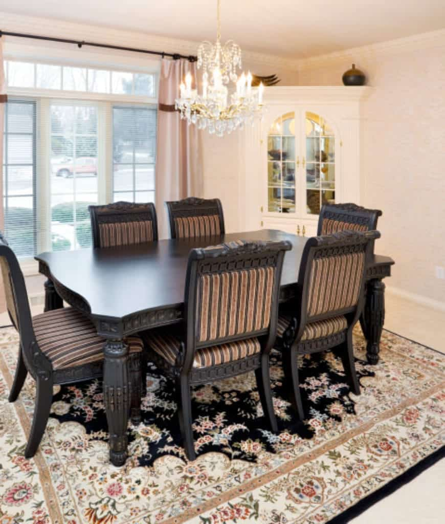 Fabulous dining room furnished with white corner display cabinet and dark wood dining set on a lovely floral rug. It has a fancy crystal chandelier and framed windows covered with blush draperies.