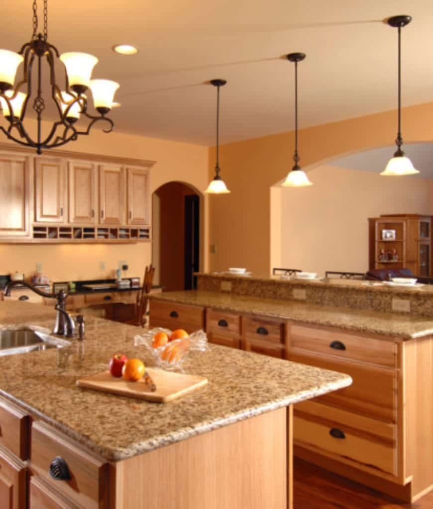 Warm kitchen with light wood cabinetry that matches with the double kitchen islands illuminated by glass dome pendants and an ornate chandelier.