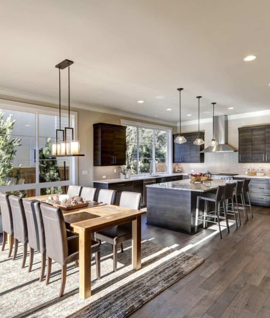 Dine-in kitchen features glass and linear pendant lights along with a wooden dining table and leather high back chairs that sit on an area rug.