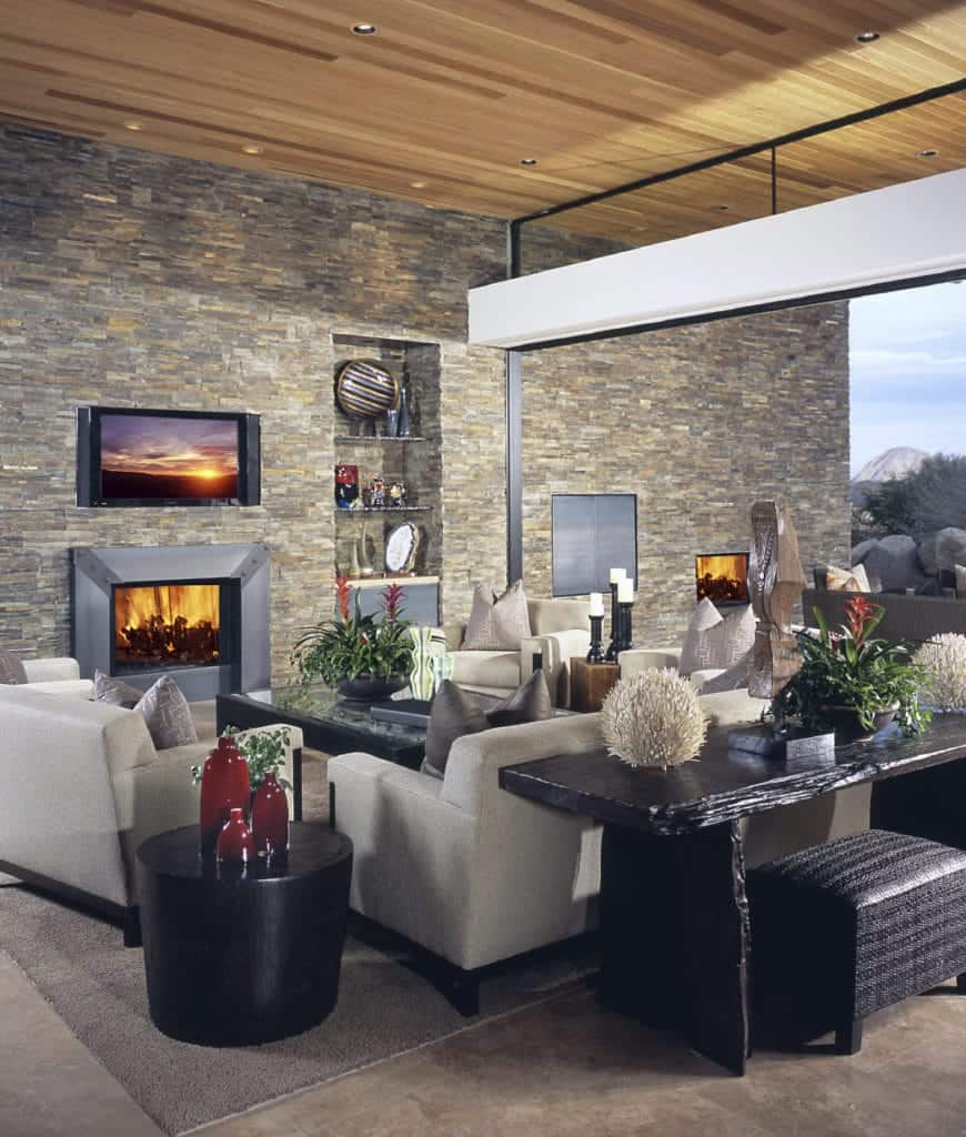Contemporary living room accented with a stone brick wall that's fitted with television, metal fireplace and inset shelves filled with various decors.