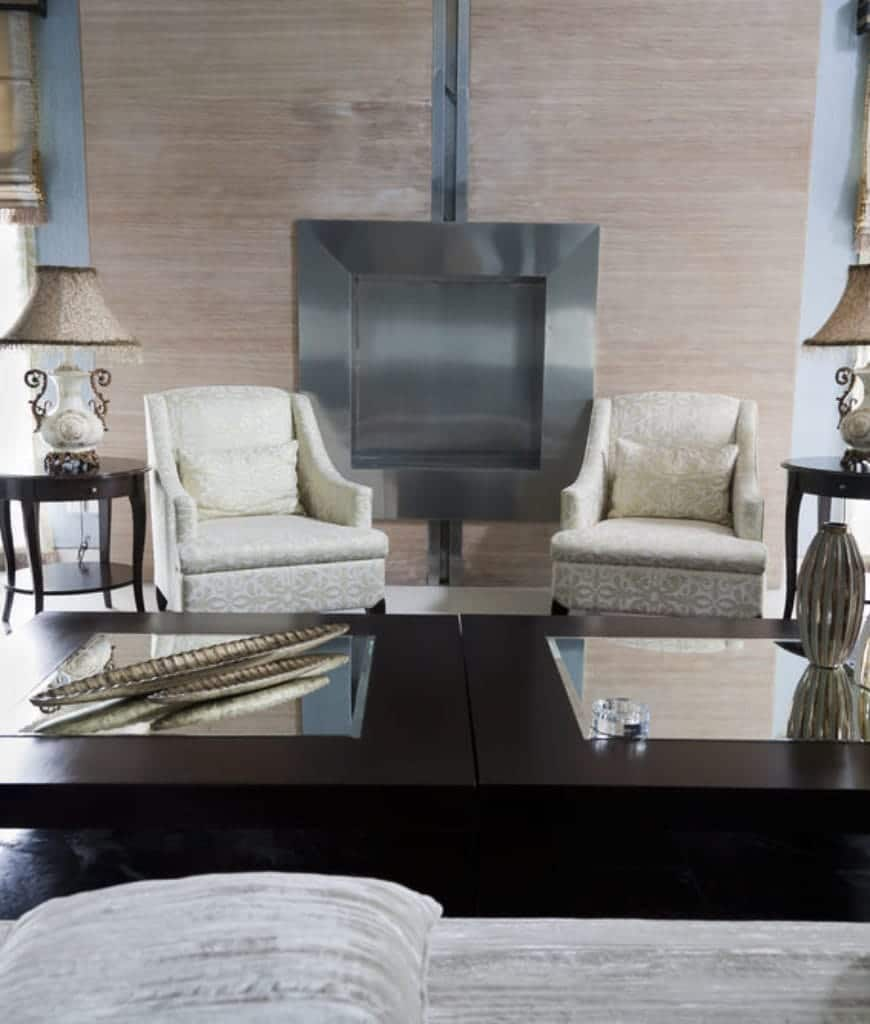 Classy living room with dark wood coffee table and white armchairs that sit in front of the aluminum fireplace fixed on the wood paneled wall.