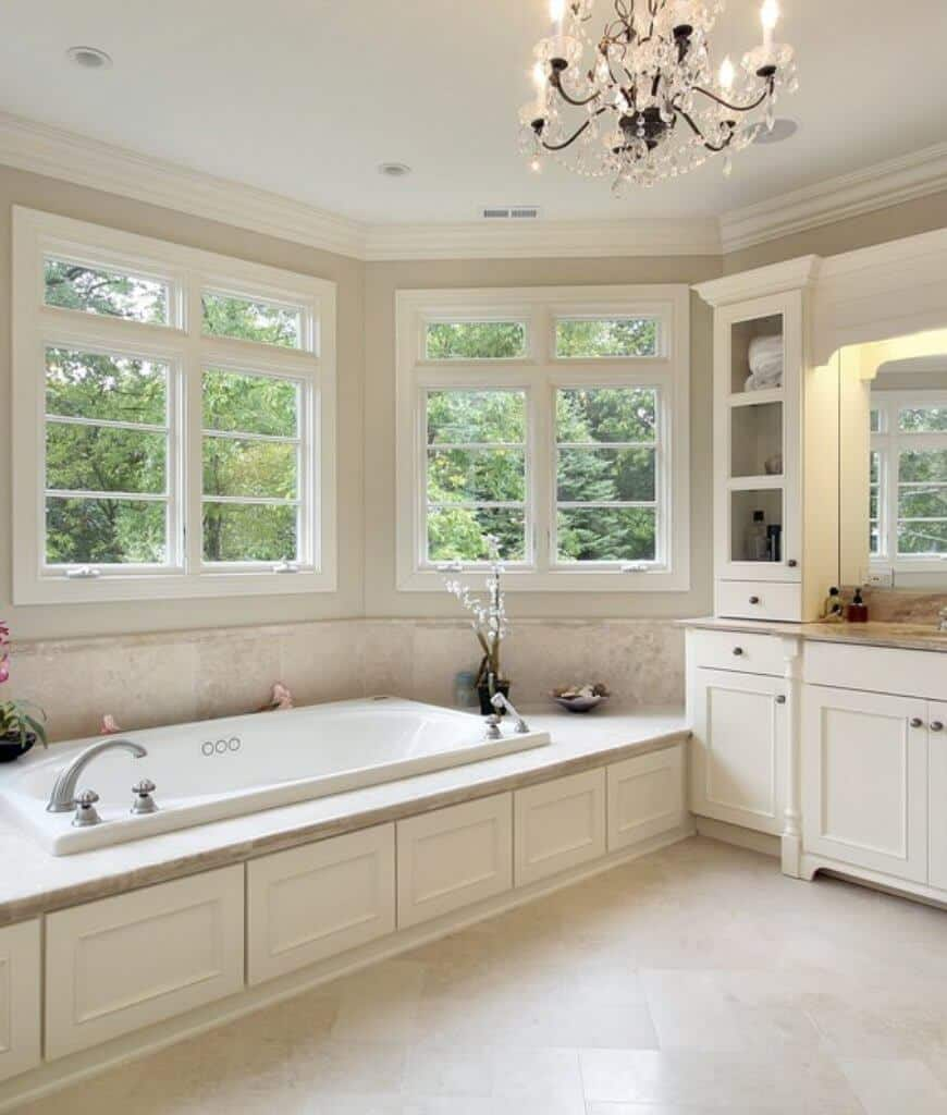 This primary bathroom boasts a gorgeous chandelier and a soaking tub adjacent to the white sink vanity with marble countertop and built-in shelving.