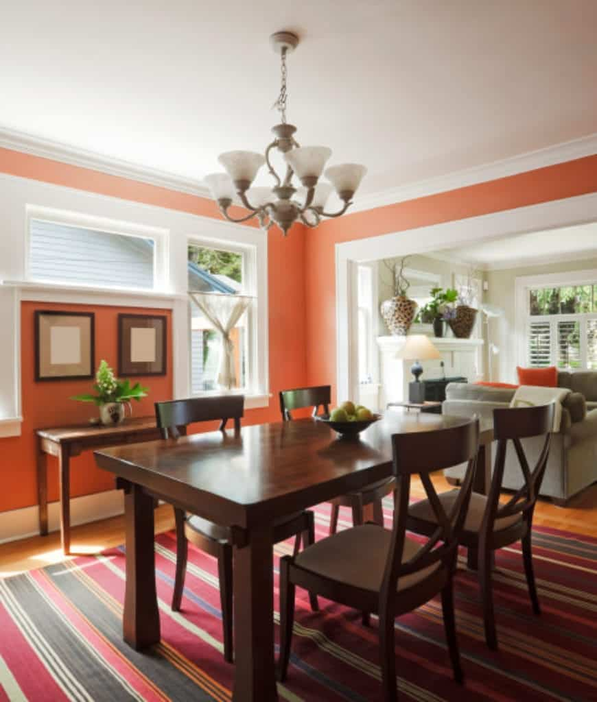 An open dining room offers a buffet table and wooden dining set accented with a red striped rug. It is illuminated by a chandelier and natural light that flows through the glazed windows.