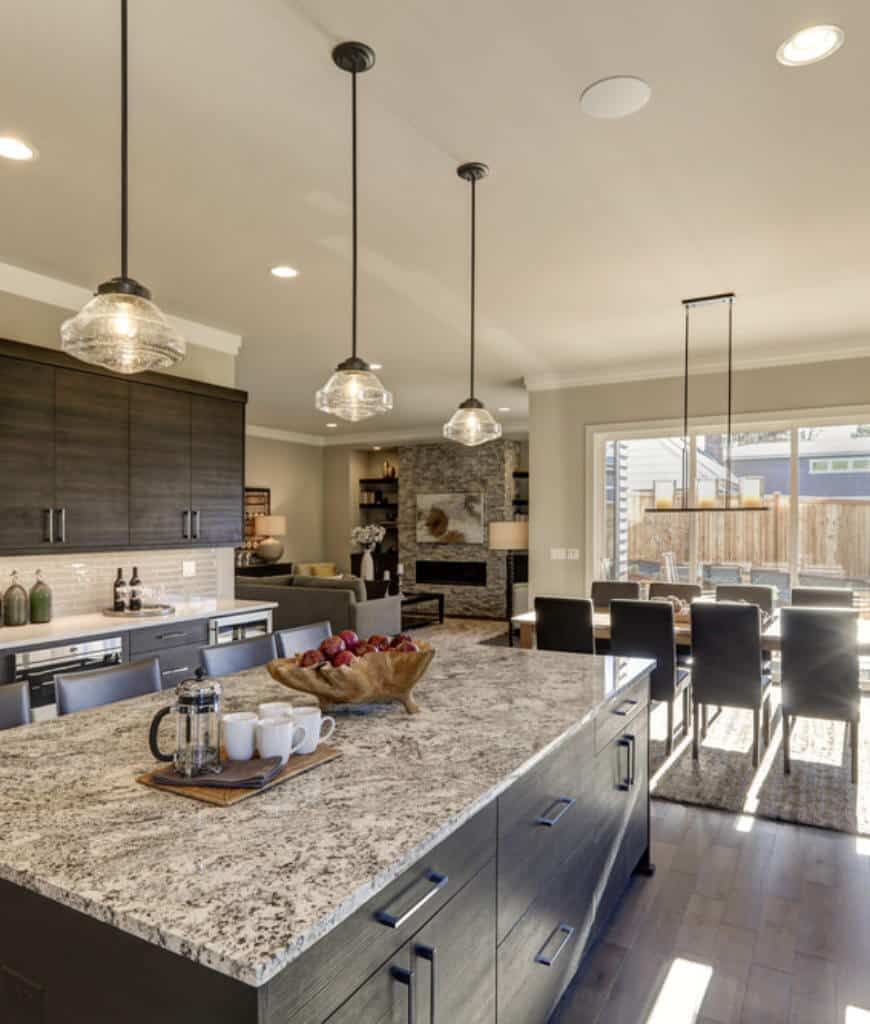 An open kitchen with natural wood plank flooring and glass sliders that open to the yard framed with wooden fence. It includes dark wood cabinetry and kitchen island lighted by glass pendants.