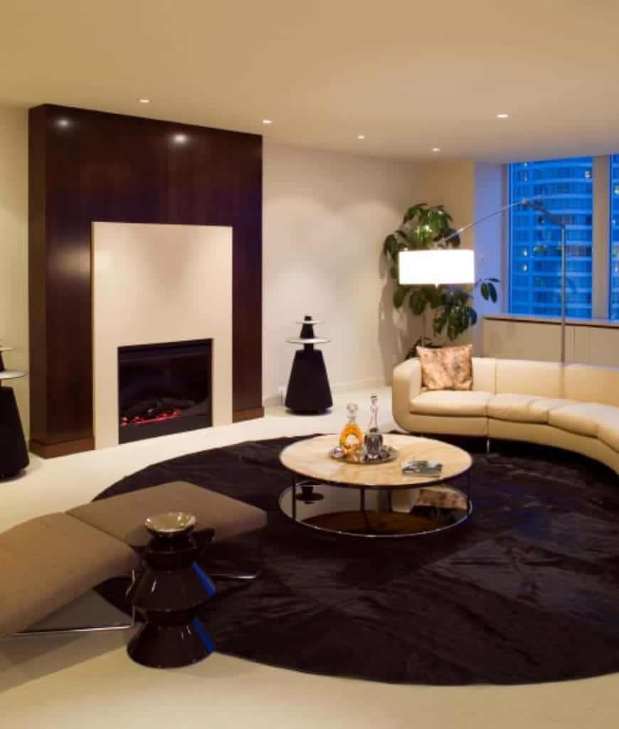 The sleek living room offers a taupe lounge chair and a round coffee table along with a curved sectional lighted by an arched floor lamp.