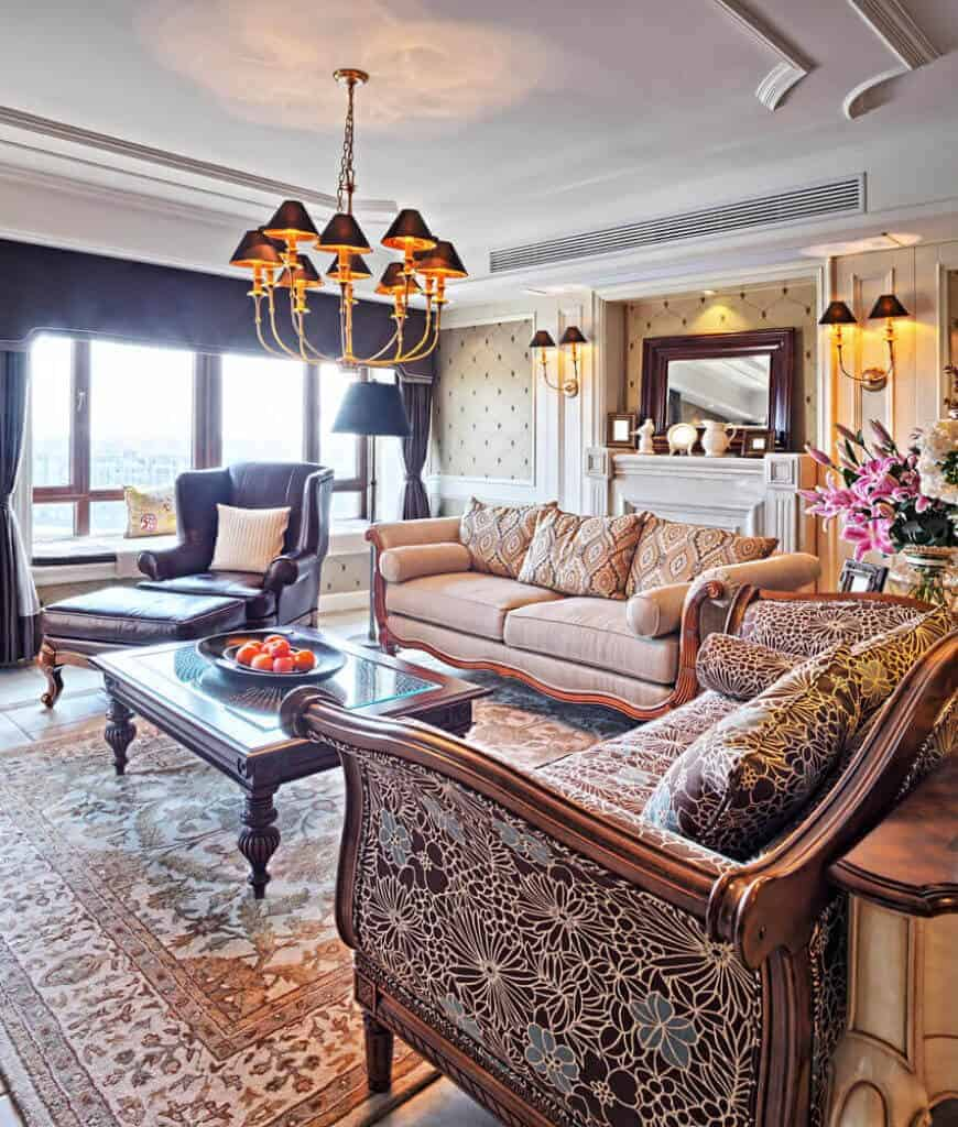 Elegant living room features classy seats and a glass top coffee table on a patterned rug. There's a fireplace behind the beige sofa lighted by wall sconces and matching chandelier.
