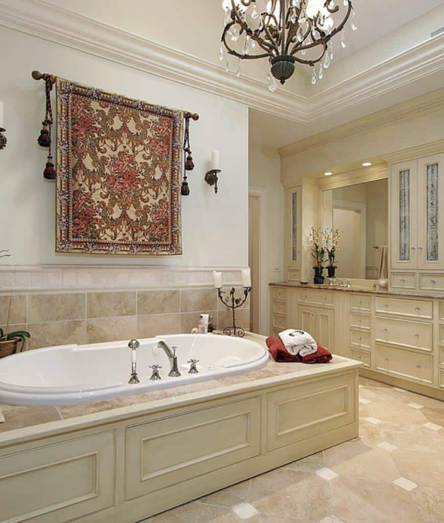 Traditional master bathroom designed with a lovely tapestry that hung above the drop in bathtub lighted by candles and a vintage chandelier.