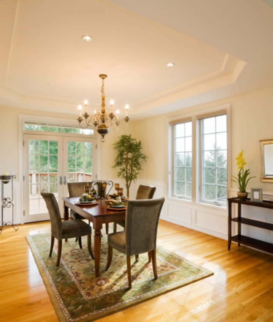 This dining room showcases a wooden dining table paired with gray chairs that sit on a green floral rug. The ambient light from the candle chandelier adds a warm vibe in this room.
