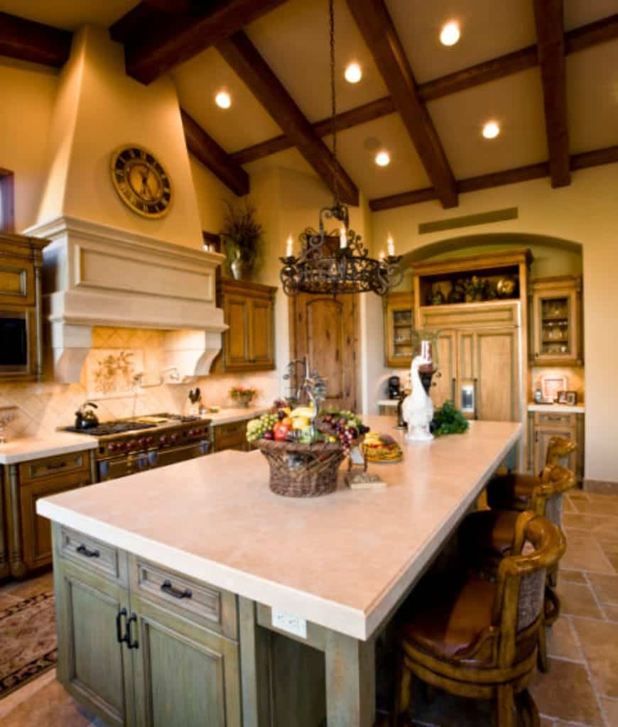 Rustic kitchen features limestone flooring and vaulted wood beam ceiling mounted with recessed lights and wrought iron chandelier.