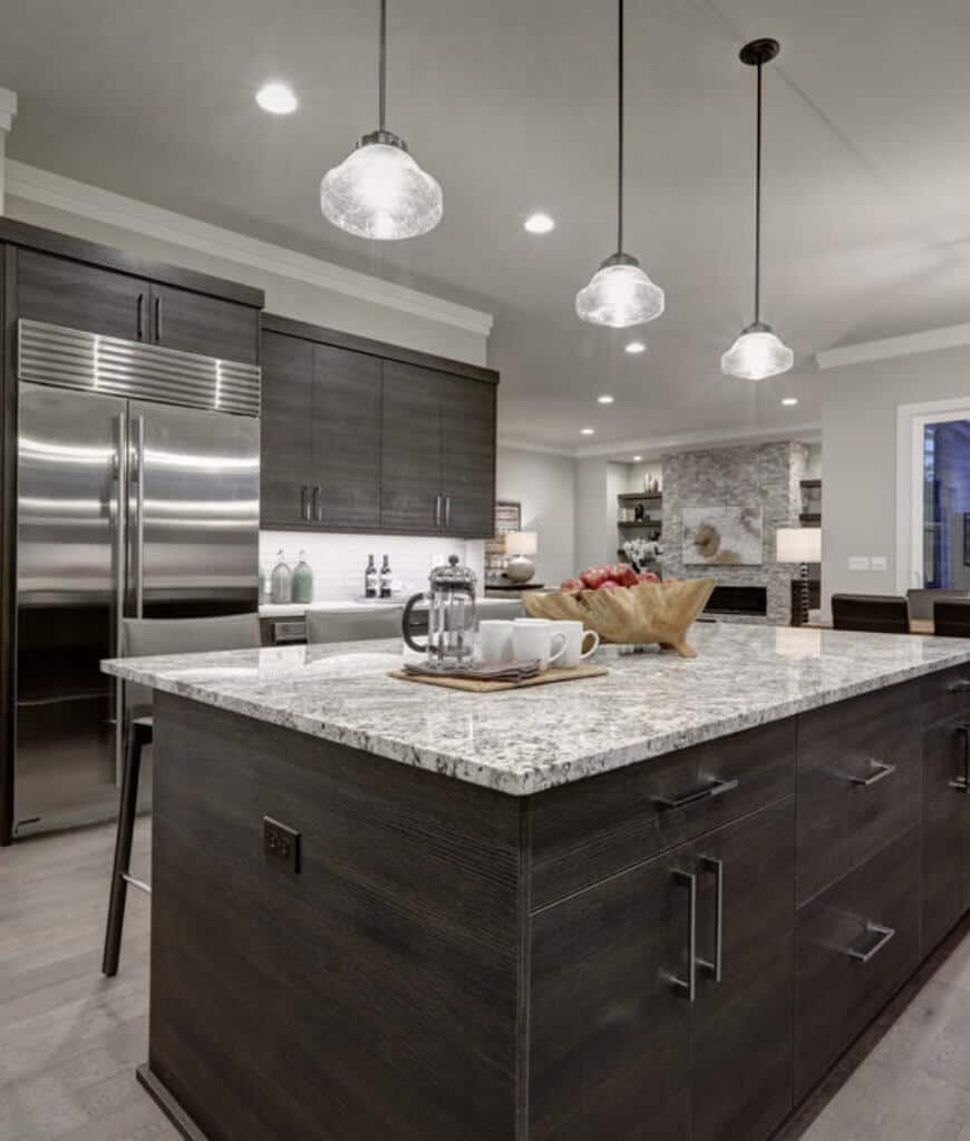 Glass pendant lights hang over the wooden breakfast island in this kitchen with dark wood cabinetry and stainless steel appliances.