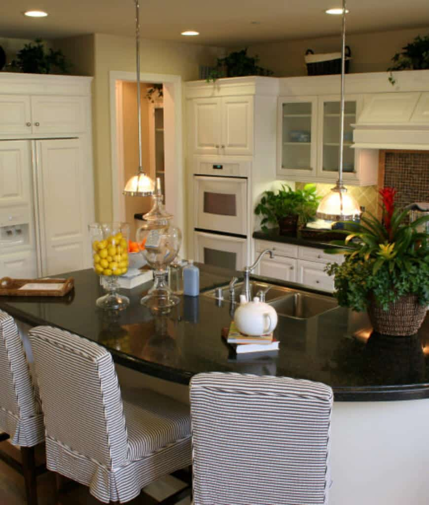 Beige kitchen features white appliances and cabinetry along with a kitchen island fitted with dual sink and paired with striped bar chairs.