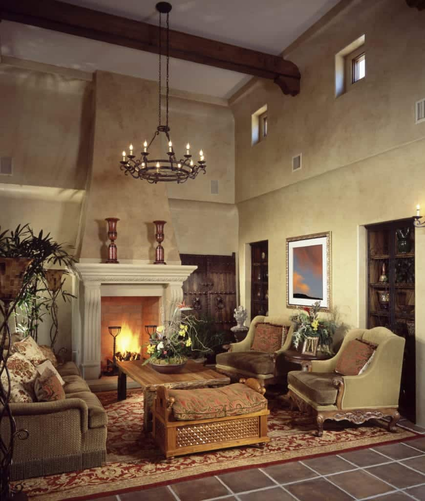 Spanish style living room features a fireplace and classy seats surrounding a wooden coffee table that sits on a red patterned rug.
