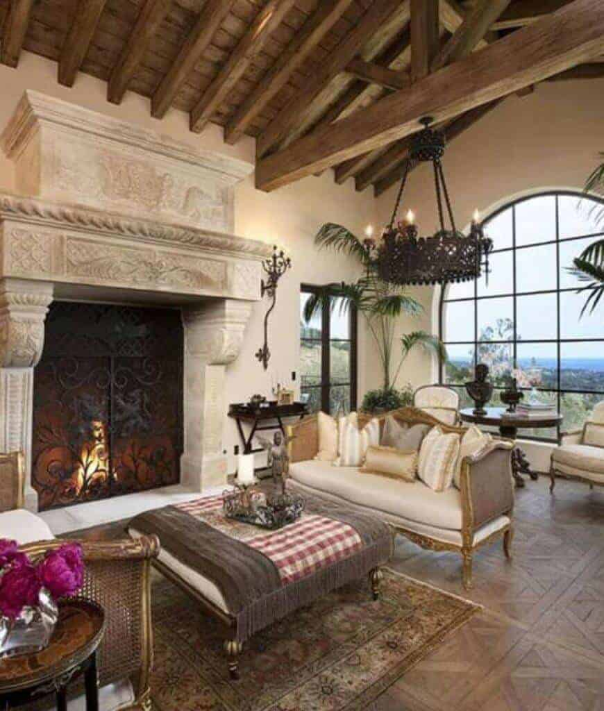 Mediterranean living room showcases elegant seats and a stone carved fireplace with intricate design. It has tiled flooring and wood beam ceiling with a hanging wrought iron chandelier.
