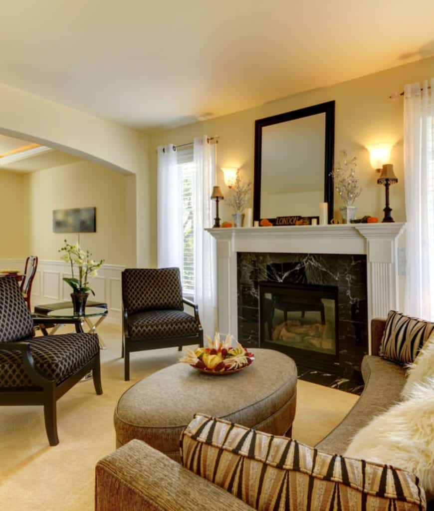 Fabulous living room features white fireplace with black marble surround tiles along with classy armchairs and a curved sofa surrounding an oval ottoman.