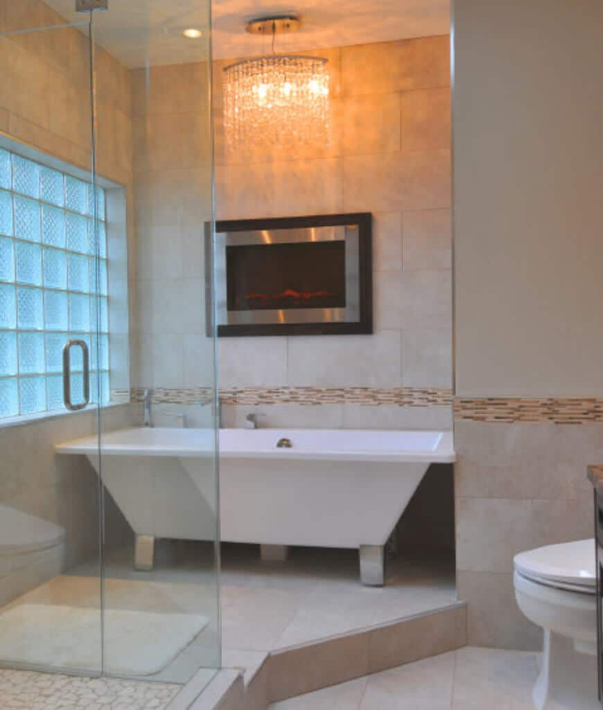 A fancy chandelier hangs over the freestanding tub in this primary bathroom showcasing a modern fireplace fixed to the marble tiled wall accented with linear mosaic tiles.