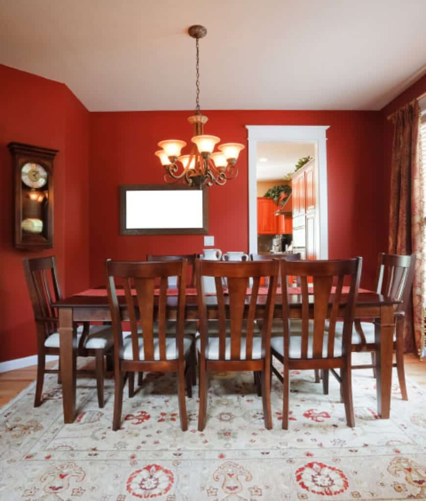 Red dining room features a patterned area rug and a rectangular dining table surrounded with matching chairs that are fitted with white cushions.