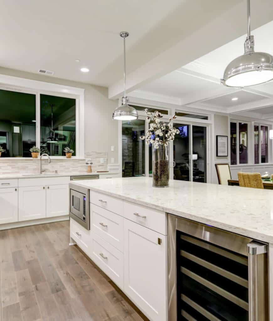 Gorgeous white kitchen boasts chrome pendant lights and an island bar over wood plank flooring fitted with an oven and wine fridge.
