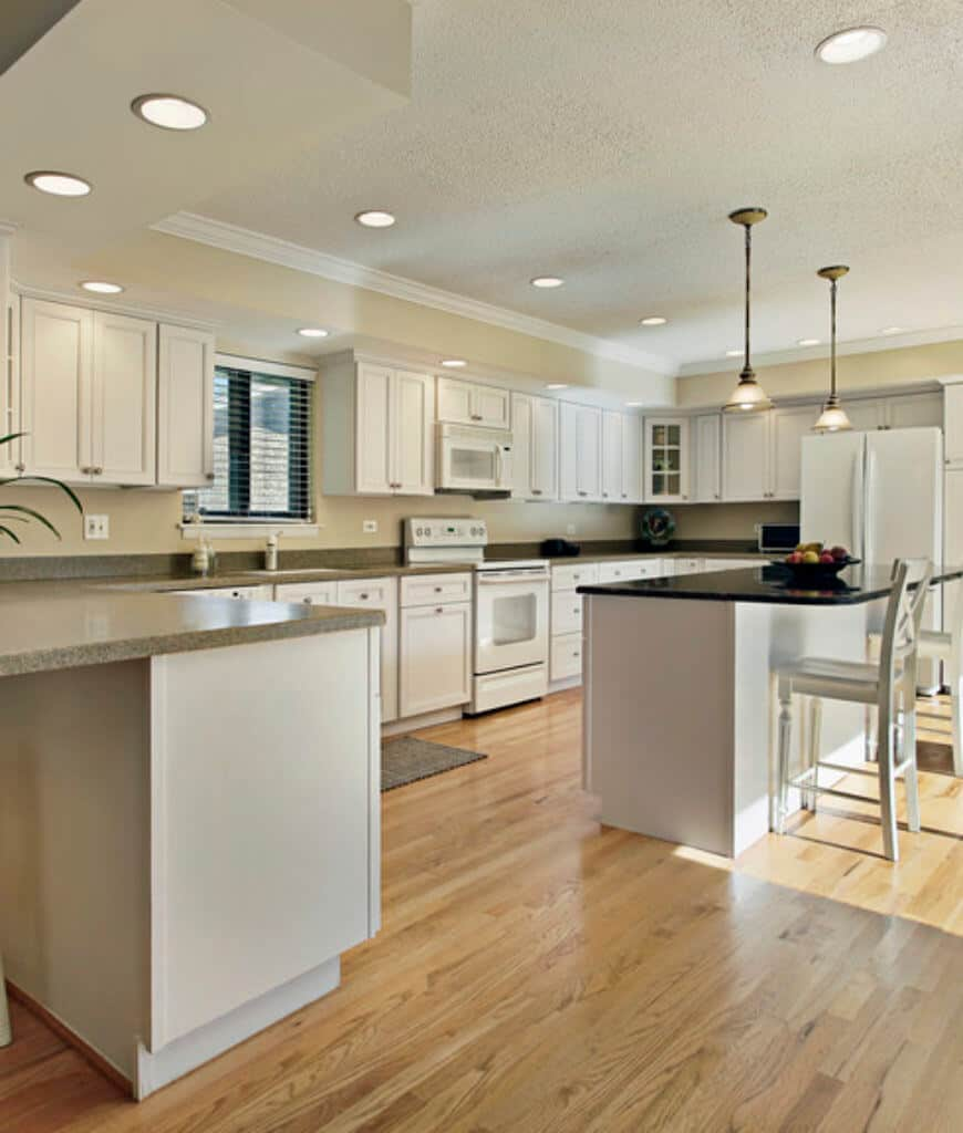 Gorgeous kitchen filled with white cabinetry and appliances along with a breakfast island lighted by glass pendants.