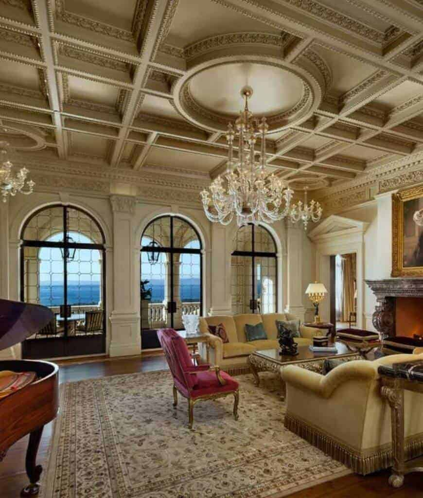 Deluxe living room accented with a pink chair that faces the fireplace topped with a framed portrait. It is illuminated by fancy chandeliers that hung from the ornate coffered ceiling.