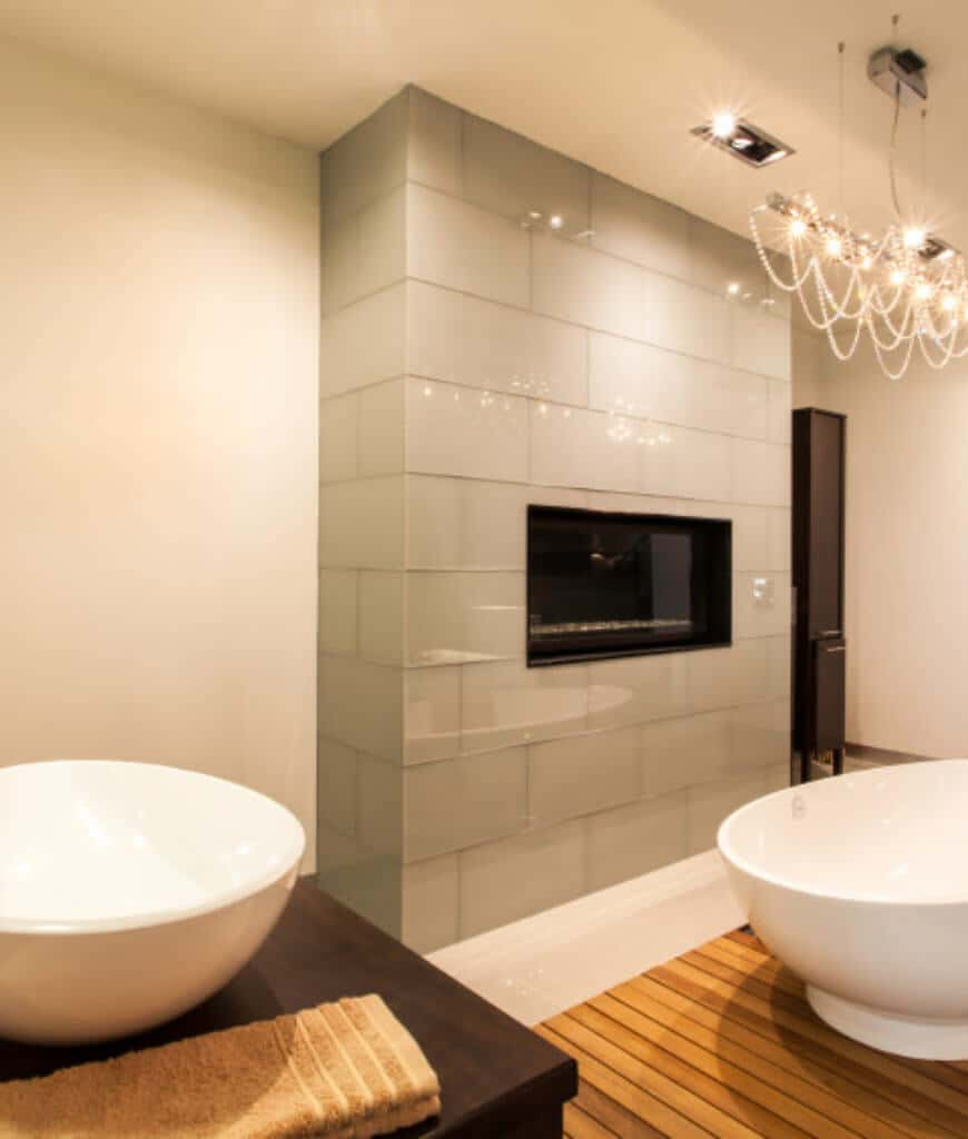A linear crystal chandelier illuminates this primary bathroom featuring a freestanding bathtub that sits on a wooden deck facing the modern fireplace fitted on the brick accent wall.