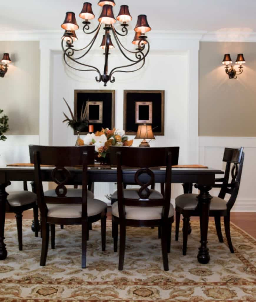 Classic dining room illuminated by wall sconces and a matching chandelier that hung over the dark wood dining set accented with a patterned rug.