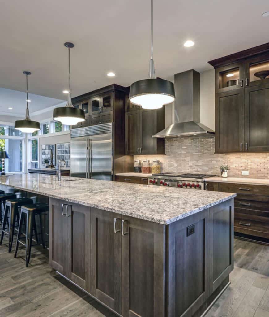 Black shade pendants illuminate this kitchen along with recessed ceiling lighting and natural light from the glazed windows. It has dark wood cabinetry that matches with the breakfast bar lined with black stools.