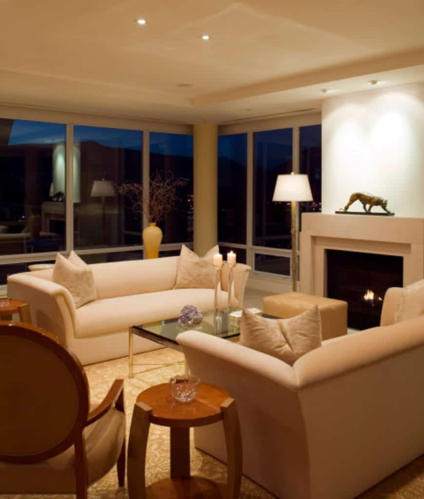 Recessed ceiling lights illuminate this living room showcasing full height glazing and facing sofas paired with glass top coffee table and a beige ottoman that sits in front of the sleek fireplace.