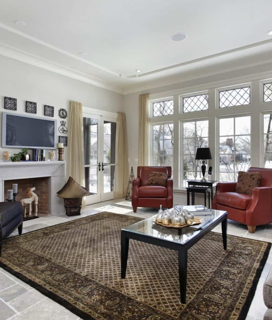 White living room accented with red leather armchairs by the glazed windows covered in sheer curtains. It has a brick fireplace and flat panel TV surrounded by ornate metal wall arts.