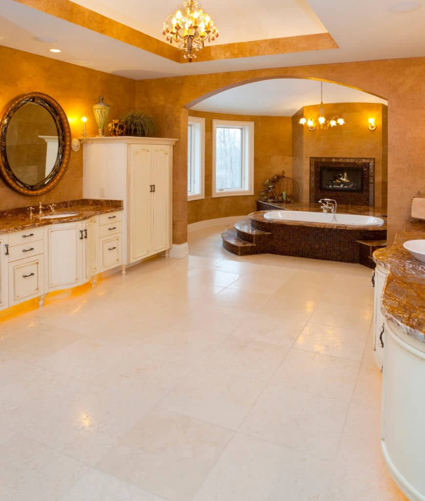 Spacious primary bathroom lighted by a warm classy chandelier that complements with the walls. It has two sink vanities facing each other along with a soaking tub by the fireplace clad in brown mosaic tiles.