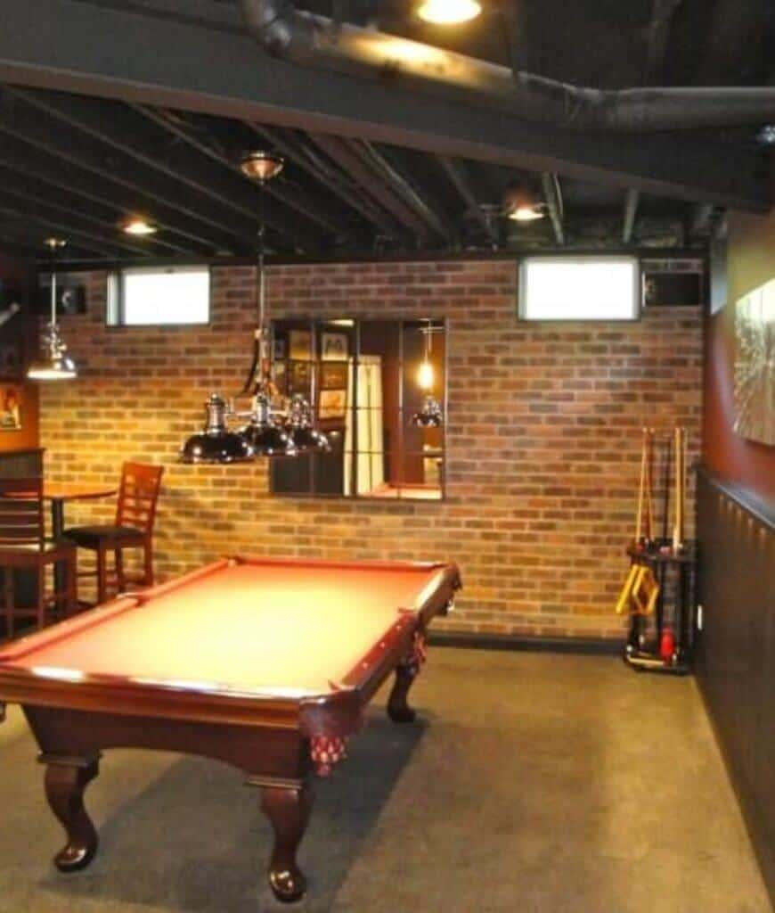 Industrial man cave with brick accent wall features a pool table illuminated by pendant lights that hung from the black ceiling lined with exposed pipes.