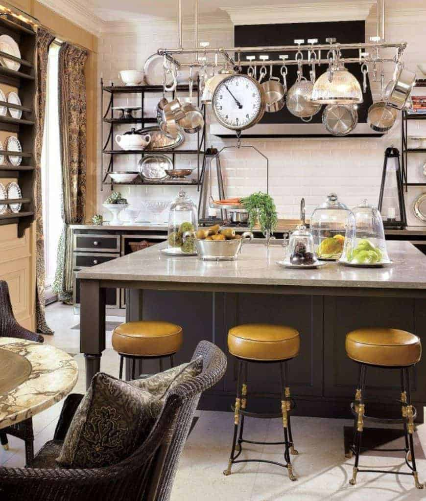 Yellow bar stools stand out in this kitchen featuring stainless steel pot rack that hung over the breakfast island. There's a black range hood in between the metal shelvings that are fixed to the white subway tile backsplash.